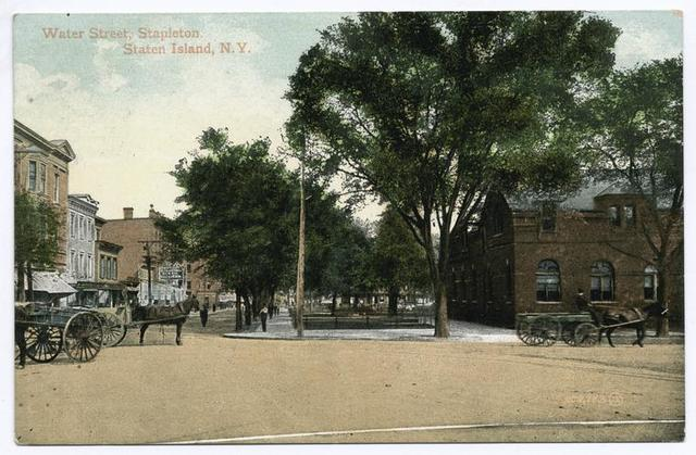 Water Street, Stapleton, Staten Island, N.Y.  [horses and wagons in street in front of park and village hall and shops]