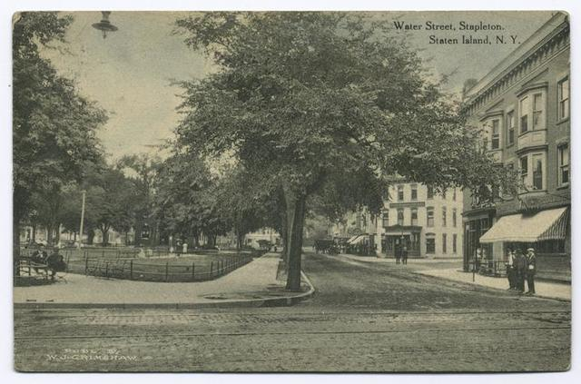 Water Street, Stapleton, Staten Island, N.Y.  [S.I. Savings Bank on corner, shops, Washington Park across street, brick road with trolley track,  men standing on sidewalk]