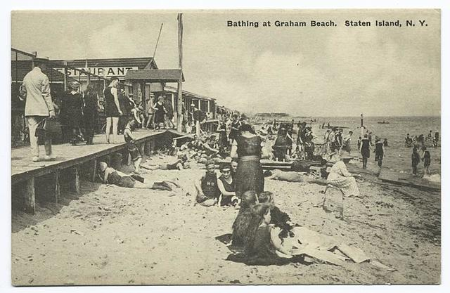 Bathing at Graham Beach, Staten Island, N.Y.  [people on sand with boardwalk and restaurant.]