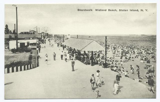 Boardwalk Midland Beach, Staten Island, N.Y. [people, waffle stand, ferris wheel in background, sun shelter.]
