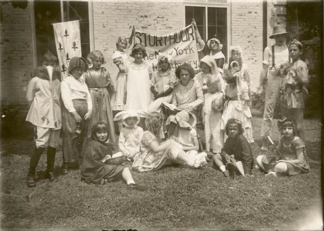 [New Dorp, Seated librarian with costumed children at story hour.]