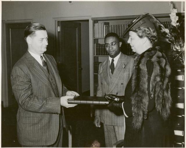 [Schomburg Collection] Mrs. Roosevelt presenting the President's manuscript copy of the radio address on the Atlantic Charter: Mr. Francis R. St. John, Chief of Circulation Department, New York Public Library; Dr. Lawrence D. Reddick, Curator of the Schomburg Collection of Negro Literature; Mrs. Franklin D. Roosevelt