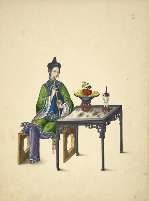 Woman seated at table, playing a xiao.