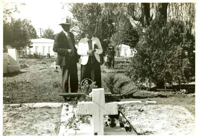 Negro couple at grave of relative; All Saint's Day in cemetery at New Roads, La.