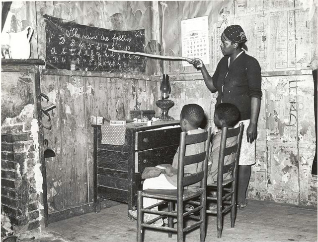 Negro mother teaching children numbers and alphabet in home of sharecropper, Transylvania, Louisiana, January 1939.