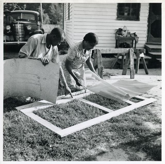 Applying the screen on the inside face of door; Demonstration of home screen door construction; Saint Mary's County, Ridge, Maryland, July 1941.