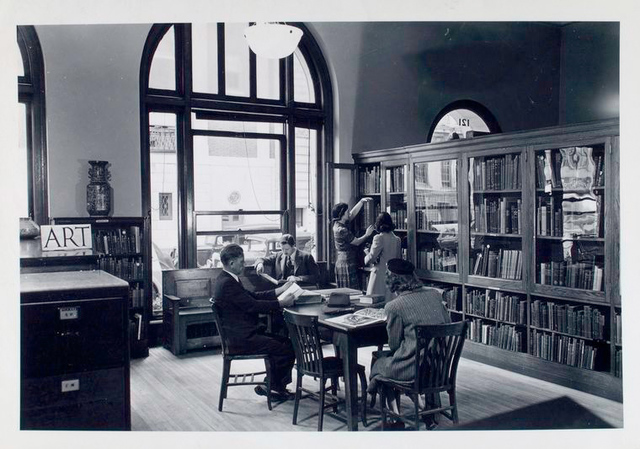 Art collection. Librarian at bookshelf with girl, others reading [58th Street Branch]