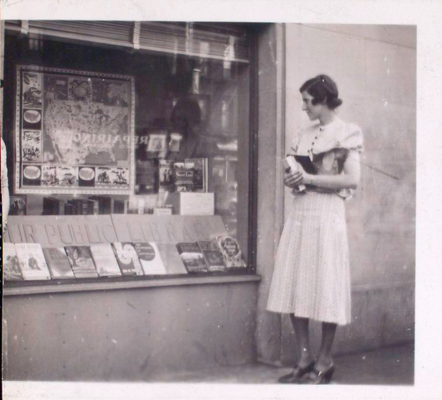 Exterior, woman looking in at window display