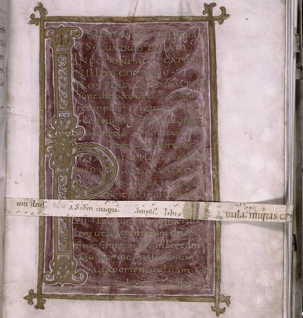 Gold uncial and caroline on purple background within gold frame.  Text for Feast of the Circumcision/Purification.  Large initial.  Strip of vellum in later hand lying across page.