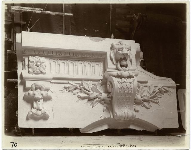 [Plaster model of architectural detail above an arch, including moldings, a keystone decorated with a volute, and a lion's head.]