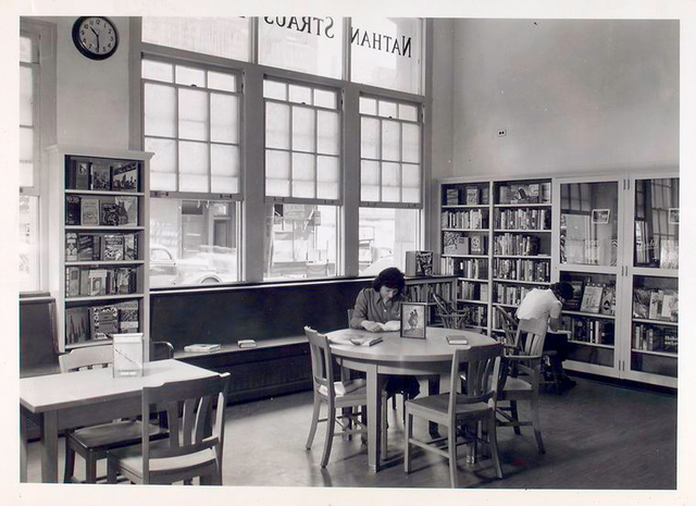Seated reader and reader at bookshelves, Donnell-Nathan Strauss
