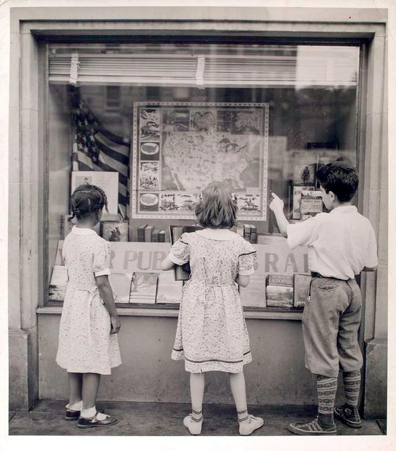[Exterior, children looking in at window display.]