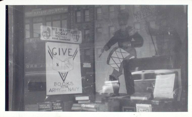 Exterior, window display asking patrons to give books to the army and navy