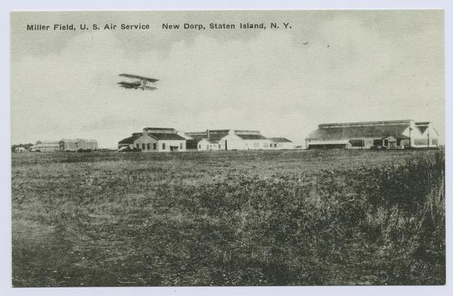 Miller Field, U. S. Air Service New Dorp, Staten Island, N.Y. [hangars, other buildings in distance, bi-plane in sky]