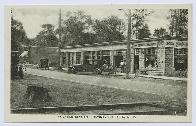 """Railroad Station, Eltingville, Staten Island, N.Y. [old cars at R.R. crossing, people on sidewalk in front of Eltingville Pharmacy with sign for soda and """"Reid's"""" ice cream]"""