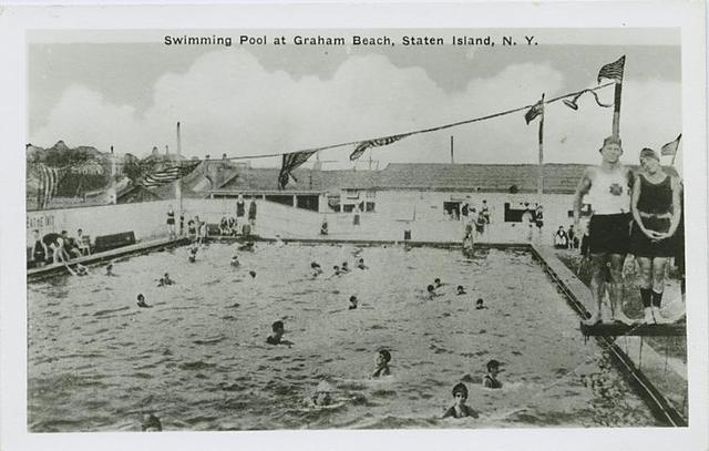 Swimming Pool at Graham Beach, Staten Island, N.Y.  [view of large pool with people swimming and posing on side, concession building or club house in background]
