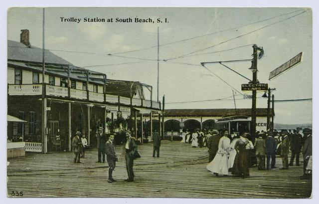 Trolley Station at South Beach, Staten Island [people in old garb standing on boardwalk by the electric car,  buildings and hotel on side and background]
