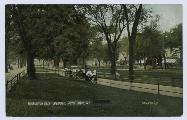 Washington Park, Stapleton, Staten Island, N.Y. (people sitting on benches along walkway, shops on street